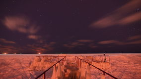 Night frozen sea ise coast and old iron pier - on moving ships and stars  timelapse stock video
