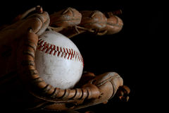Night game. Baseball mitt and vintage hardball in black Royalty Free Stock Photography