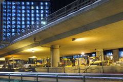 Night Garage. At night, when they are not in use, the machines are put away under a bridge, passing below a modern building stock photos