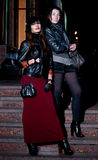 Night girls. Urban strobe portrait of pretty young brunette female models wearing leather jackets, black stockings, shorts, gray scarf, black hat, red skirt Stock Image