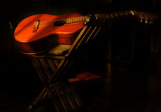 Night guitar. Acoustic guitar laying on top of a chair, very low light scene Royalty Free Stock Images