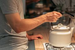 Night habit insomnia tea man putting kettle stove. Night habit and insomnia. Tea preparation. Cropped shot of man putting old style kettle on stove stock photo