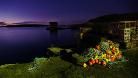 Night at the harbor. Night at a small harbor with fishing nests and equipment royalty free stock photography