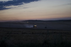 Night harvest, harvesters are reaping on a wheat field. Royalty Free Stock Image