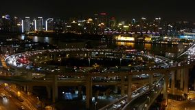 Night heavy traffic jam on overpass interchange,Brightly lit cityscape,shanghai. Aerial freeway busy city rush hour heavy traffic jam highway Shanghai at night stock footage