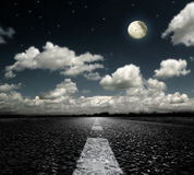 Asphalted road clouds and moon Royalty Free Stock Image