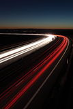 Night highway rush. Night highway (Cars in a rush moving fast on a highway (speedway) at the nightfall Royalty Free Stock Photography