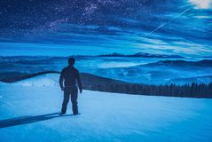Night hiker. Hiker standing on a hill covered with snow and enjoy starry sky above the winter mountain valley Stock Photo