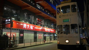 Night Hong Kong street with double-decker tram passing by. HONG KONG - NOVEMBER 09, 2015: Night street in the city. Double-decker tram passing by and cars stock video