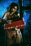 Night horror. Bloodthirsty witch standing at the night cemetery and holding a coffin Stock Image