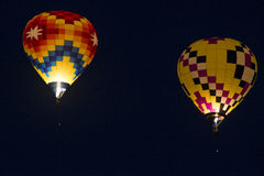 Night Hot-Air Balloon Flight. 2 hot air balloons take flight to create a glowing light show Stock Photo