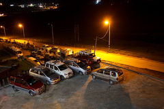Night hotel car parking lot. A hotel car parking lot at night with parked suv and cars with a road and street light of yellow tungsten color Royalty Free Stock Images