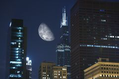 Night Hours in Chicago. Large Moon Between Skyscrapers. Urban Photo Collection Stock Photos