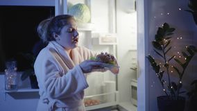 Night hunger, young girl in dressing gown in the kitchen opens the fridge and eagerly bites a burger then go away in