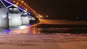 Night illuminated bridge and river with ice at night stock video footage