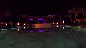 Night illuminated pool. Dolly shot. Changing colored lights at night pool stock video