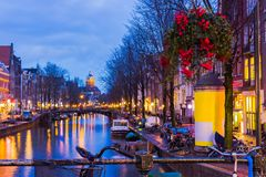 Night illumination of Amsterdam canal and bridge with typical dutch houses, boats and bicycles. Night illumination of Amsterdam canal and bridge with typical Royalty Free Stock Images