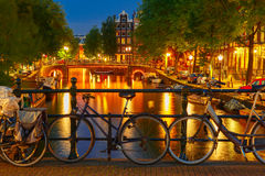 Night  illumination of Amsterdam canal and bridge Stock Photos