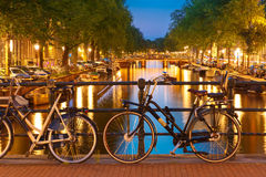 Night illumination of Amsterdam canal and bridge. With typical dutch houses, boats and bicycles, Holland, Netherlands stock images