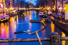 Night illumination of Amsterdam canal and bridge with typical dutch houses, boats and bicycles. Royalty Free Stock Photos