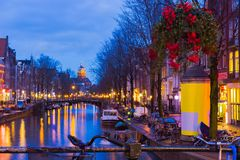 Night illumination of Amsterdam canal and bridge with typical dutch houses, boats and bicycles. Night illumination of Amsterdam canal and bridge with typical Royalty Free Stock Photography