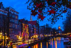 Night illumination of Amsterdam canal and bridge with typical dutch houses, boats and bicycles. Royalty Free Stock Photography