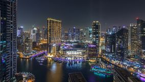 Night illumination of Dubai Marina aerial timelapse, UAE. Modern skyscrapers and residential buildings. Traffic on the road. Yachts and boats near shoping mall stock video