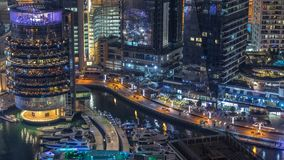 Night illumination of Dubai Marina aerial timelapse, UAE. Modern skyscrapers and residential buildings. People walking on promenade. Yachts and boats near stock video footage