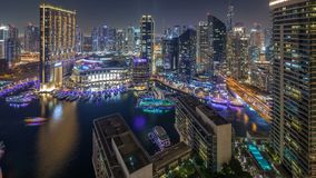 Night illumination of Dubai Marina aerial timelapse, UAE. Modern skyscrapers and residential buildings. Traffic on the road. Yachts and boats near shoping mall stock video footage