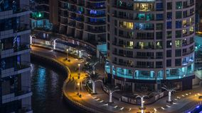 Night illumination of Dubai Marina aerial timelapse, UAE. Modern skyscrapers and residential buildings. People walking on promenade. Yachts and boats near stock footage