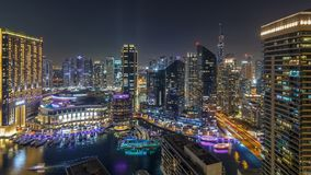 Night illumination of Dubai Marina aerial timelapse, UAE. Modern skyscrapers and residential buildings. Traffic on the road. Yachts and boats near shoping mall stock footage