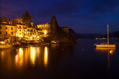 Night on lake Como harbor, illuminated buildings a Stock Images