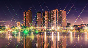 Night at a lake of a park with the city on background. City lights with star effect reflected on water. Landscape of a beautiful dusk at Parque das Nacoes royalty free stock images