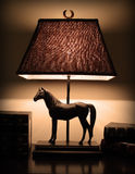 Night lamp on the desk. Night lamp with horse design and books on the desk Stock Images