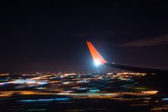 Night landing approach airport over city lights, view of the wing of the aircraft, shooting with a long exposure Royalty Free Stock Image