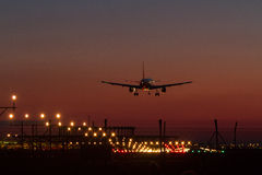 Night landing. Of a commercial aircraft at the airport Stock Images