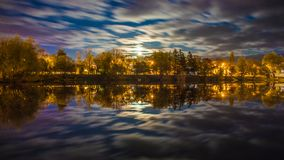 Night landscape above river with trees lit by city lights and clouds in motion royalty free stock images