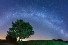 Night landscape with colorful Milky Way stars over the tree silhouette. Starry sky with hills at summer. Beautiful Universe. Space astro photography background royalty free stock photos