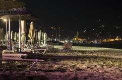 Night landscape with a deserted beach and night illumination Amoudara, Greece. Night landscape with a deserted beach with sun loungers and parasols and night royalty free stock image