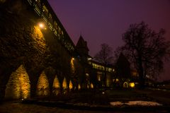 Night landscape of fortress walls with lighting. The Former Prison Tower Neitsitorn In Old Tallinn, Estonia. Maiden Tower. Night landscape of fortress walls with stock photo