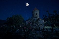 Mysterious medieval castle and the cathedral church at night on a background of the full moon. Night landscape of full moon over the old albanian church in Sheki royalty free stock photo