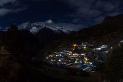 Night landscape in high mountains. Night view of mountain small town Namche Bazaar, Nepal; Kongde Ri peak in the moonlight (Himalayas Royalty Free Stock Photo
