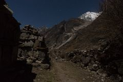 Night landscape in Langtand valley trek. Old wall ruins and snow peaks at night Stock Photo