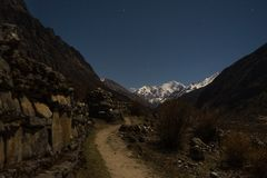 Night landscape in Langtand valley trek. Old wall ruins and snow peaks at night Stock Images
