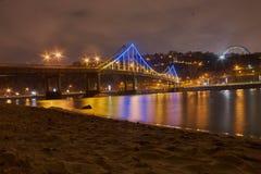 Night landscape. Luminous pedestrian bridge. On the Dnieper River. Kiev, Ukraine Stock Images