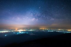 Night landscape of Milky way above the light of countryside area and mountain.  stock photos