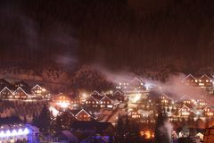 Night landscape with mountain village near forest. In winter royalty free stock photography