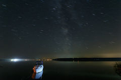 Free Night Landscape Of Lake With Moored Boat And Sky With Star Trails Stock Image - 78411221