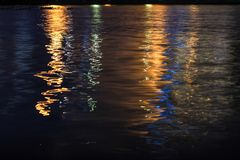 Night landscape, sea, colored lights reflected in Royalty Free Stock Photo