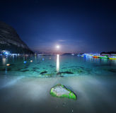 Night landscape at the sea with stone, yellow sand and lunar path. Moonrise. Travel background. Stock Image
